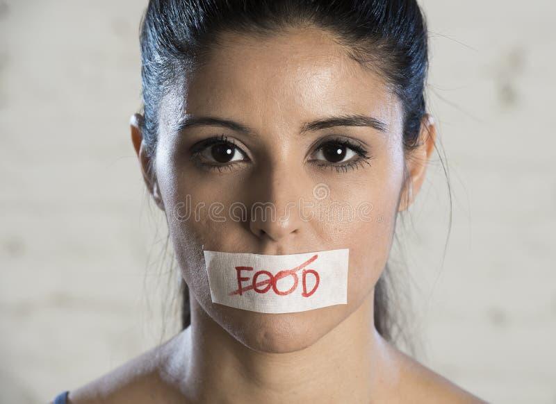 Chiuda sul fronte di giovane bella donna latina triste con la bocca sigillata su nastro del bastone con il testo nessun alimento immagine stock