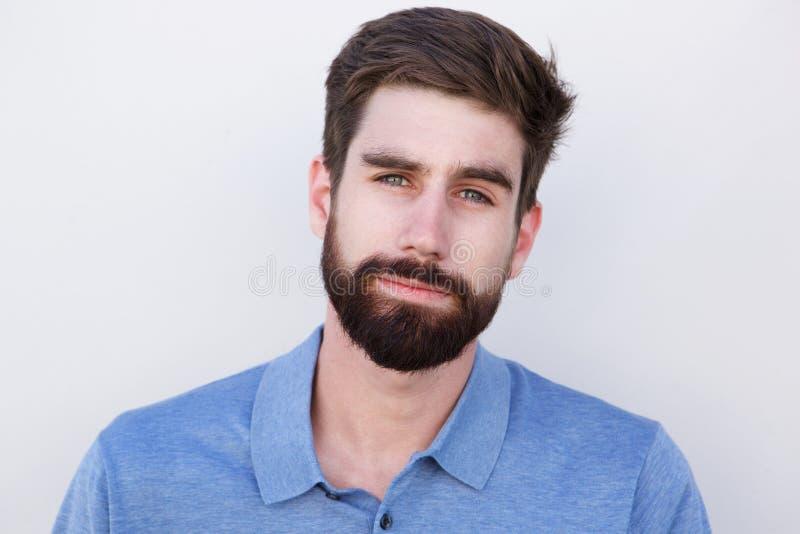 Chiuda sul giovane bello con la barba contro fondo bianco fotografia stock libera da diritti