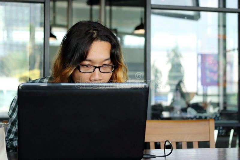 Chiuda sul giovane lavoratore asiatico che guarda il suo computer portatile in ufficio contro il fondo dello spazio della copia fotografia stock