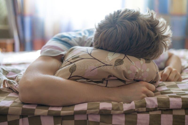 Chiuda sul giovane maschio che si trova sul sonno del letto nel mroning contro il throung del sole la finestra f immagini stock libere da diritti