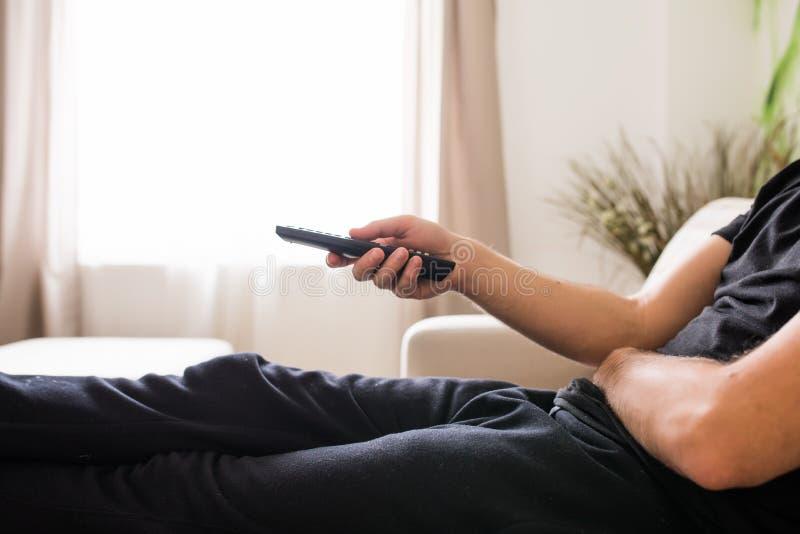 Chiuda sul giovane uomo barbuto che si siede sullo strato mentre commutano i canali televisivi Fuoco su telecomando fotografie stock
