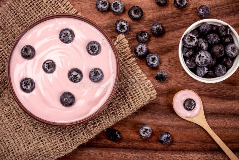 chiuda sul jogurt alla frutta casalingo cremoso rosa dei mirtilli con la foglia verde fresca della menta su fondo bianco, sulla v fotografia stock