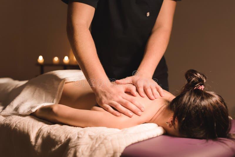 Chiuda sul lavoratore manuale maschio che fa il massaggio della stazione termale ad una ragazza in una stanza scura fotografia stock