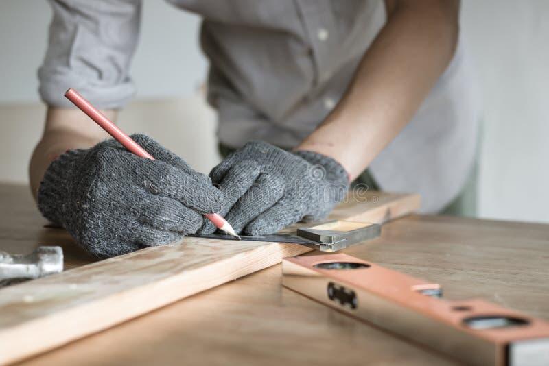 Chiuda sul legno della misura del carpentiere, la giovane misura di fabbricazione maschio o fotografia stock