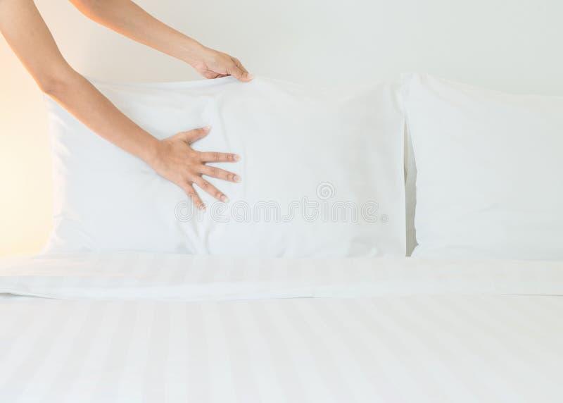 Chiuda sul lenzuolo bianco installato mano nella camera di albergo fotografie stock