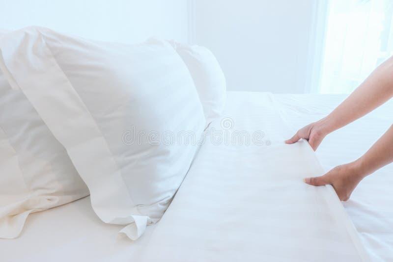 Chiuda sul lenzuolo bianco installato mano nella camera di albergo, fuoco selettivo immagini stock