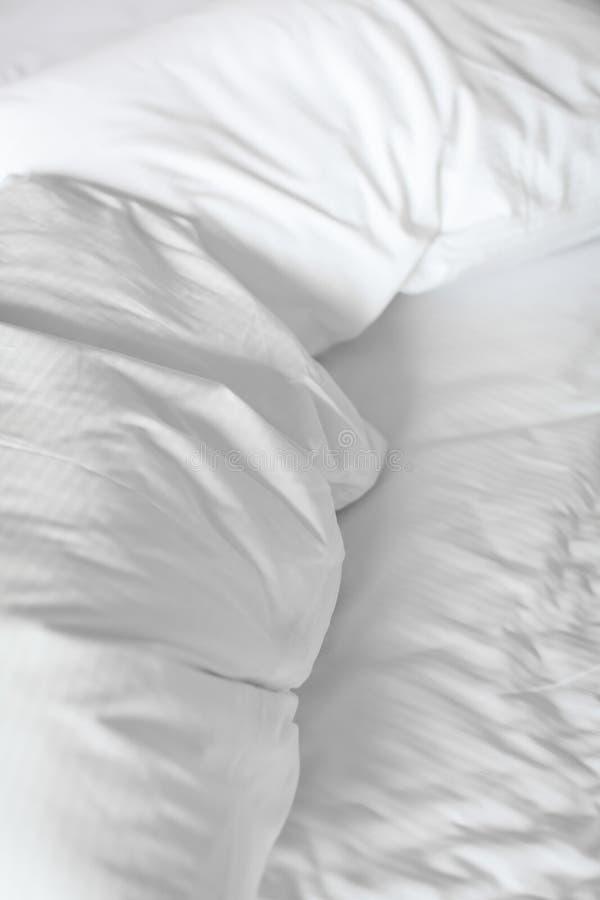 Chiuda sul letto con il lenzuolo, la coperta ed i cuscini sgualciti dopo che sonno del piumino della comodità che sveglia di matt immagine stock
