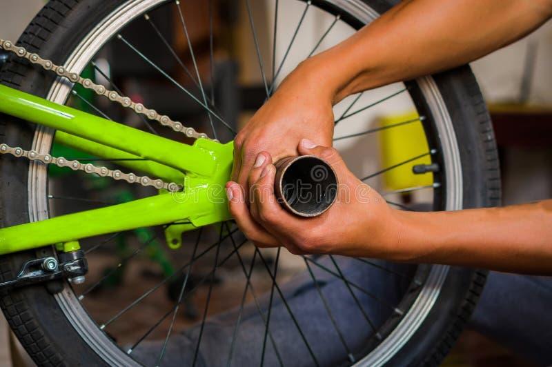 Chiuda sul meccanico che ripara la ruota che aggiunge un tubo in un'officina, nel fondo vago fotografie stock libere da diritti