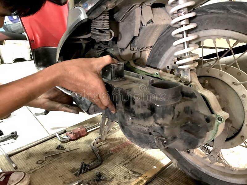 Chiuda sul meccanico di automobile che ripara il motociclo fotografia stock