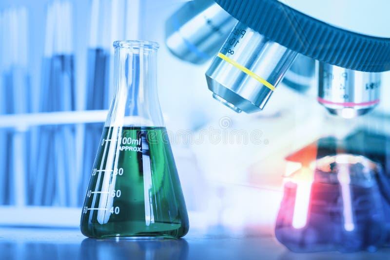 Chiuda sul microscopio con la vetreria per laboratorio, resea del laboratorio di scienza immagine stock libera da diritti