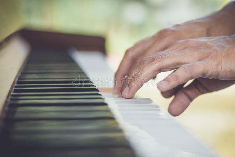 Chiuda sul musicista della mano dell'uomo che gioca il piano fotografia stock libera da diritti