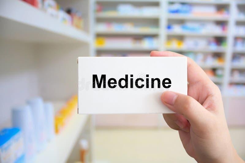 Chiuda sul pacchetto della scatola della medicina della tenuta della mano del farmacista immagine stock libera da diritti