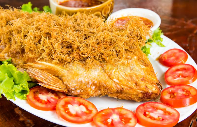 Chiuda sul pesce fritto con l'erba servita con la fetta fresca del pomodoro e la salsa piccante sul piatto bianco sulla tavola immagini stock