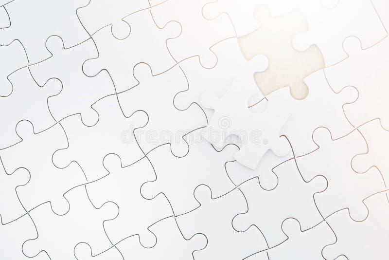 Chiuda sul pezzo non finito di puzzle bianco Completi il puzzle con i pezzi e la luce solare mancanti di mattina fotografia stock