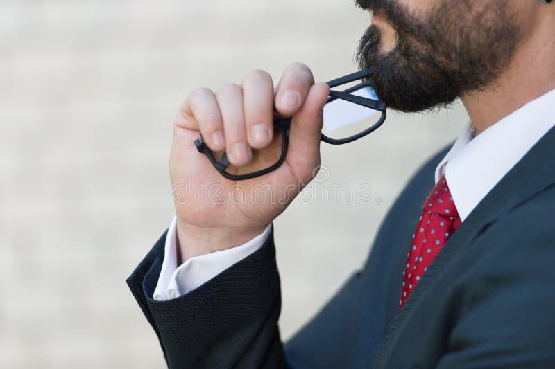Chiuda sul profilo dell'uomo d'affari barbuto e passi tiene i vetri Uomo in vestito blu ed in legame rosso che pensa sopra la nuo fotografia stock