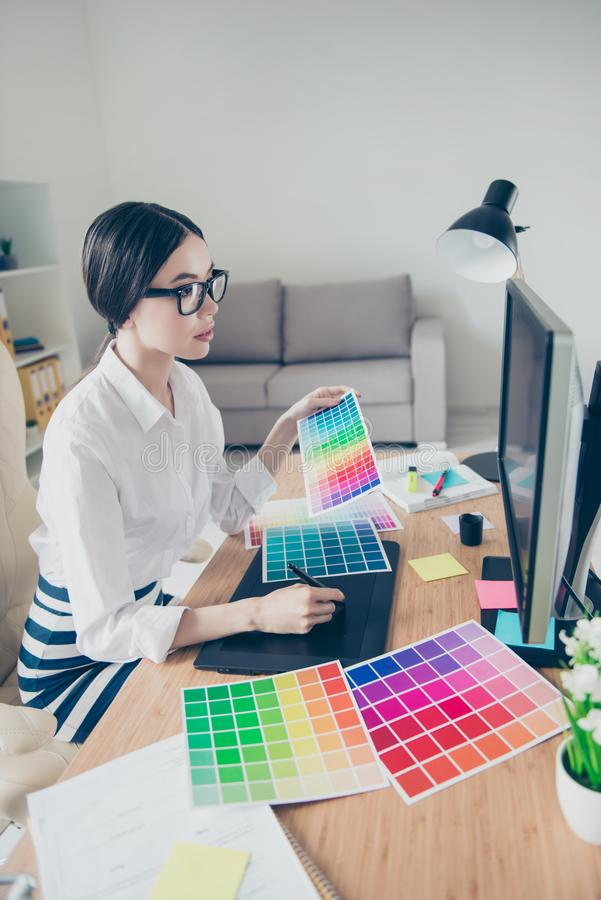 Chiuda sul profilo laterale di giovane progettista asiatico occupato di animazione, il Dott. immagini stock