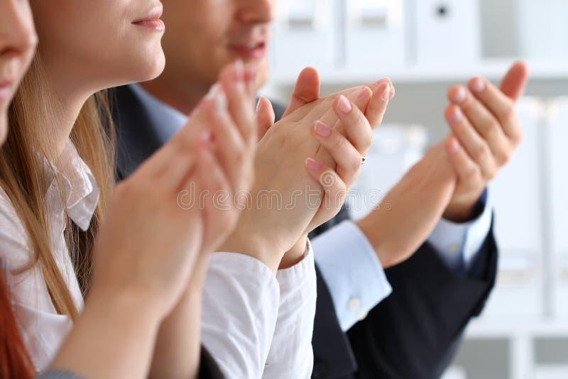 Chiuda sul punto di vista degli ascoltatori di seminario di affari che applaudono le mani fotografia stock