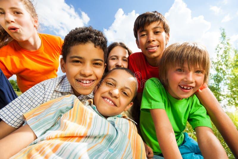 Chiuda sul punto di vista dei bambini sorridenti in un abbraccio fotografia stock