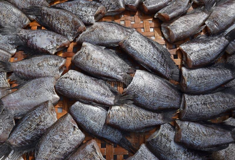 Chiuda sul punto di vista del pesce essiccato senza testa chiamato Pla Salit sul canestro di bambù rotondo immagini stock libere da diritti
