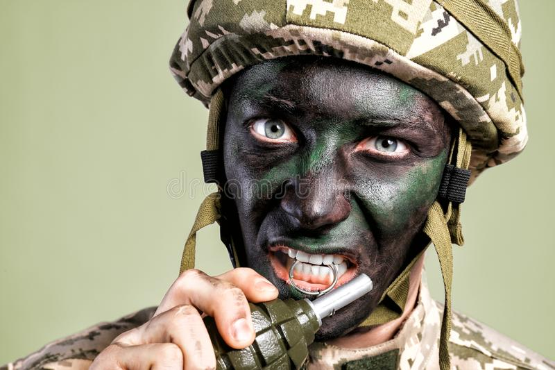 Chiuda sul punto di vista del soldato che estrae la spilla di sicurezza fotografia stock