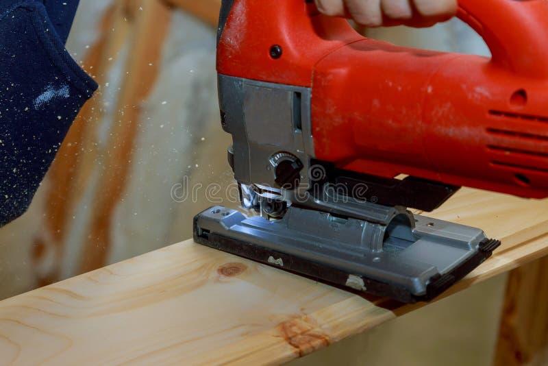Chiuda sul puzzle elettrico che taglia un pezzo di legno immagini stock
