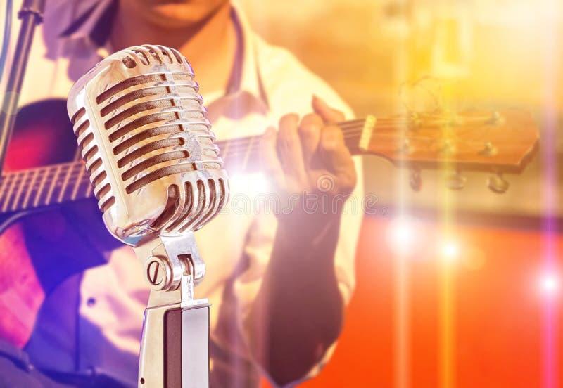 Chiuda sul retro microfono con il musicista che gioca la chitarra acustica sulla banda immagini stock libere da diritti