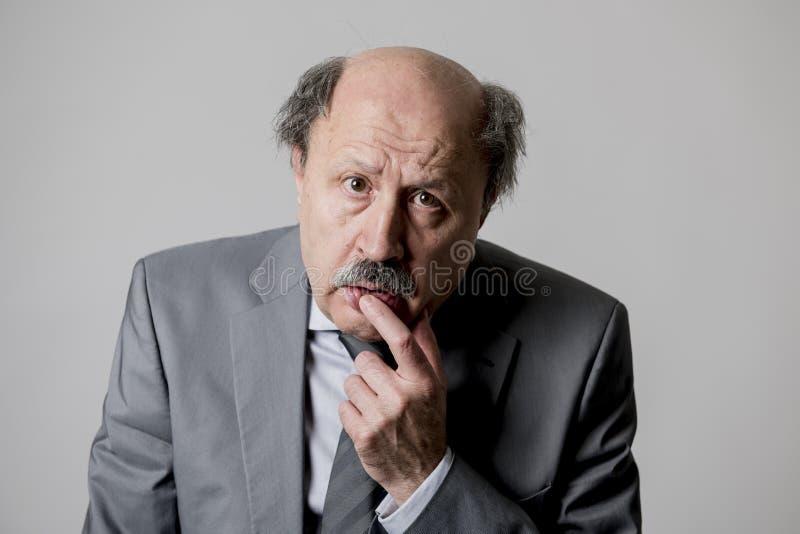 Chiuda sul ritratto capo di sguardo triste e depresso senior calvo dell'uomo di affari 60s divertente e sudicio nell'emozione di  immagine stock