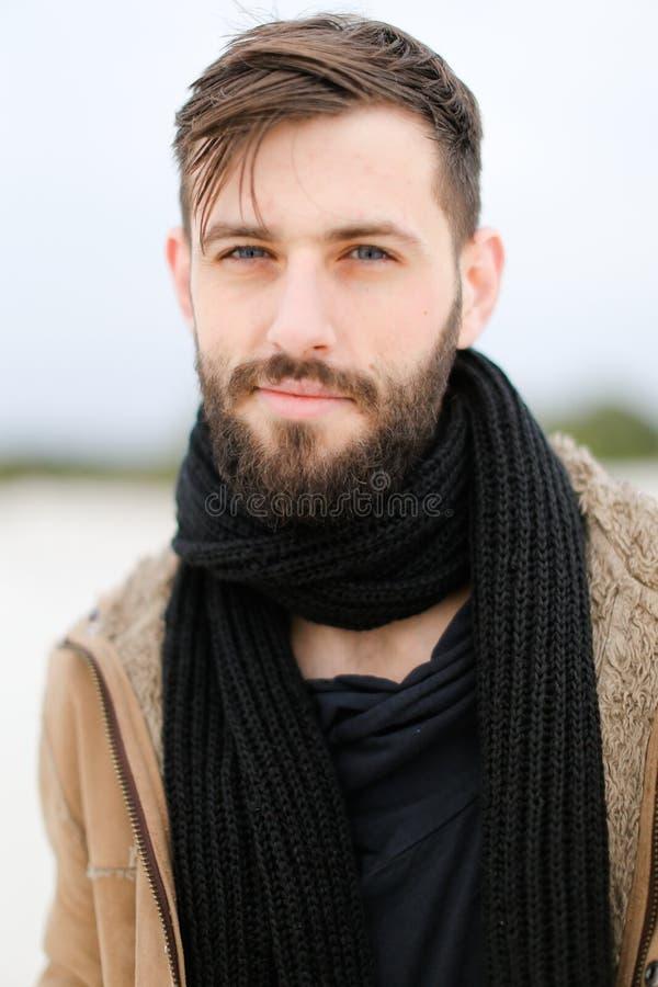 Chiuda sul ritratto del giovane con il cappotto d'uso della barba e la sciarpa nera che stanno nel fondo bianco dell'inverno fotografia stock libera da diritti