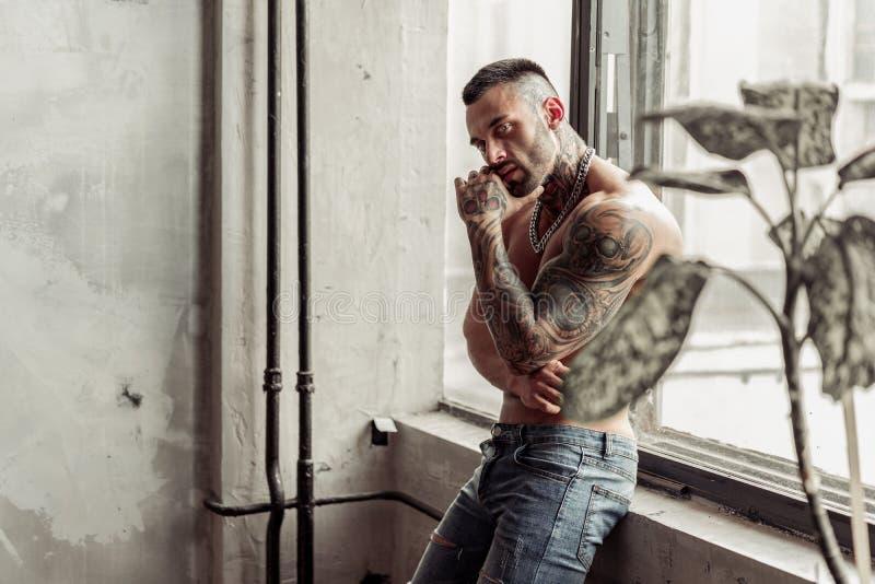 Chiuda sul ritratto del modello maschio nudo sexy con il tatuaggio e gli occhi magici che stanno nella posa calda sopra vicino al immagini stock libere da diritti