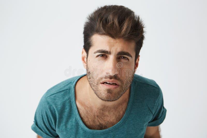Chiuda sul ritratto del tipo ispanico maturo nello sguardo scettico della maglietta blu in camera, provante a distinguere la sua  fotografia stock
