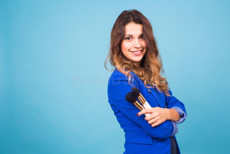 Chiuda sul ritratto del truccatore con le spazzole su fondo blu fotografie stock libere da diritti