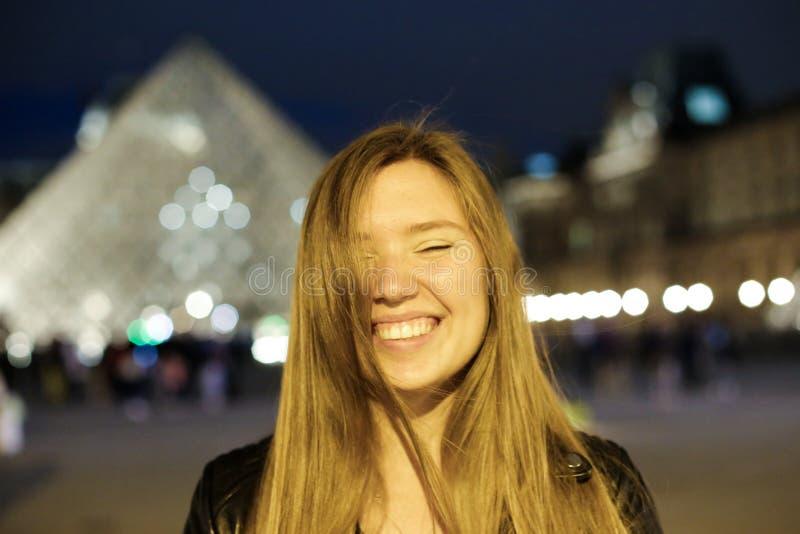 Chiuda sul ritratto del turista femminile nel oyramid di vetro nel fondo, Parigi fotografia stock