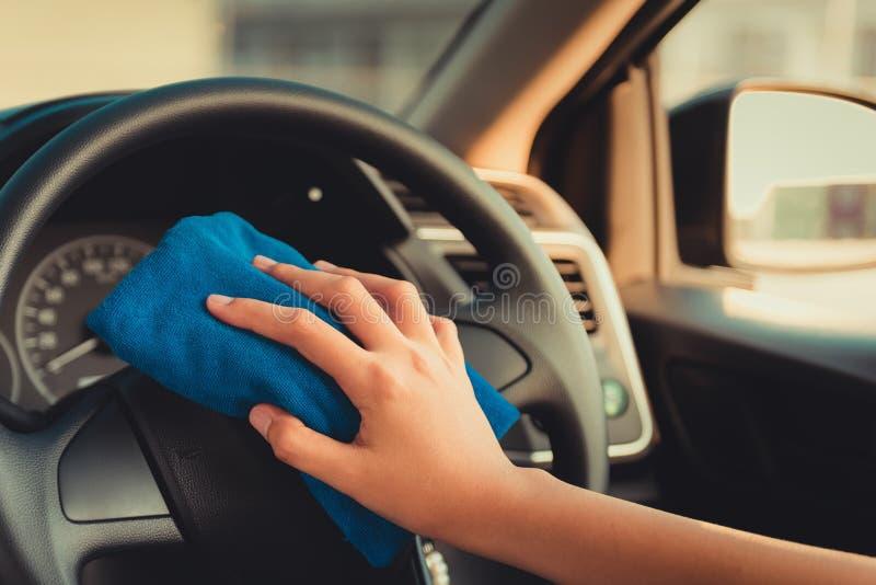 Chiuda sul ritratto del volante dell'automobile di pulizia della mano della donna immagine stock