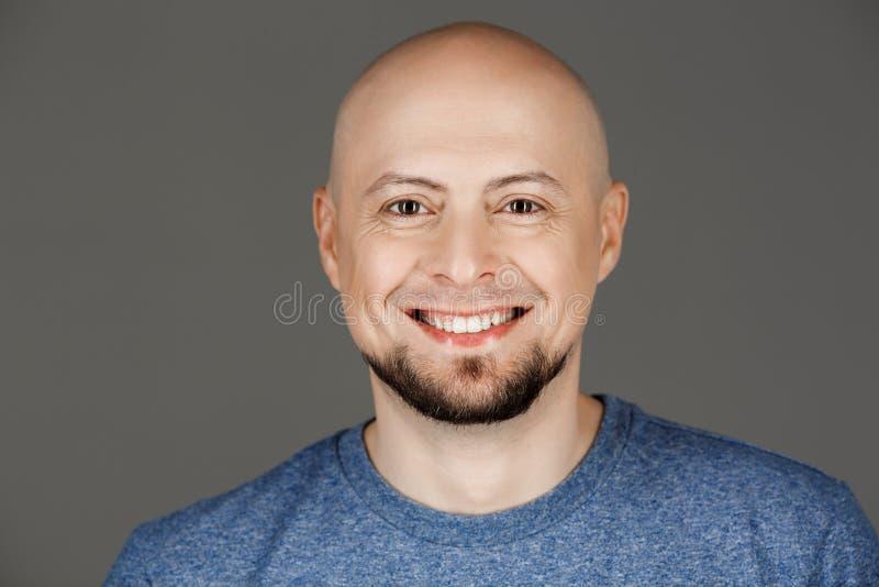 Chiuda sul ritratto dell'uomo di mezza età bello in camicia grigia che sorride alla macchina fotografica sopra fondo scuro immagini stock