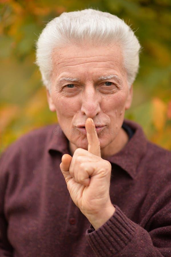 Chiuda sul ritratto dell'uomo senior con il dito sulle labbra immagine stock
