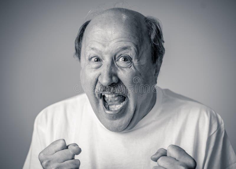 Chiuda sul ritratto dell'uomo senior sorpreso e felice che celebra la vittoria e la lotteria wining fotografia stock