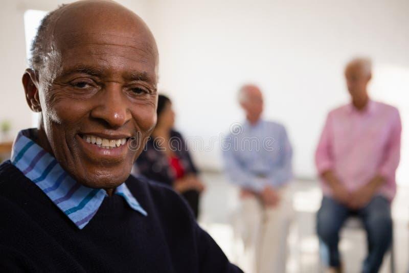 Chiuda sul ritratto dell'uomo senior sorridente con gli amici nel fondo immagine stock libera da diritti