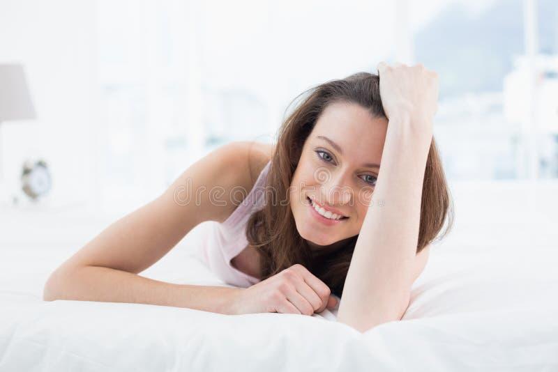 Chiuda sul ritratto della donna abbastanza felice che riposa a letto immagine stock