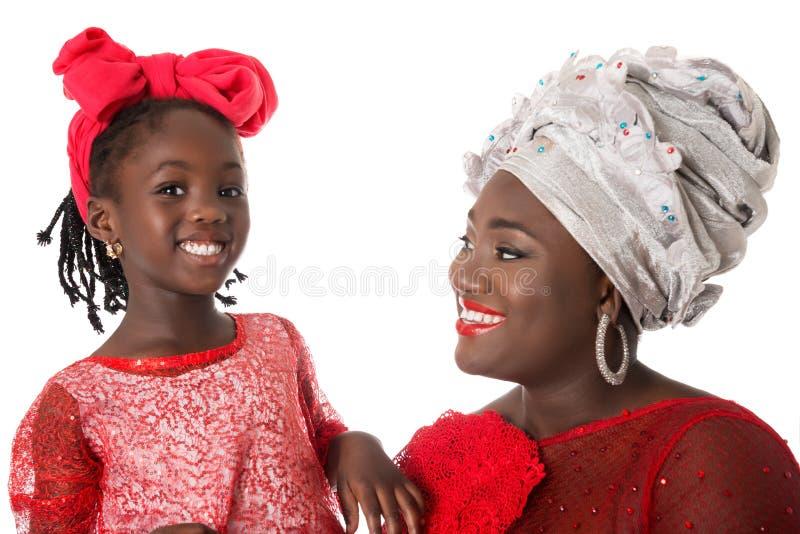 Chiuda sul ritratto della donna africana con la bambina in abbigliamento di rosso di tradizione immagine stock libera da diritti