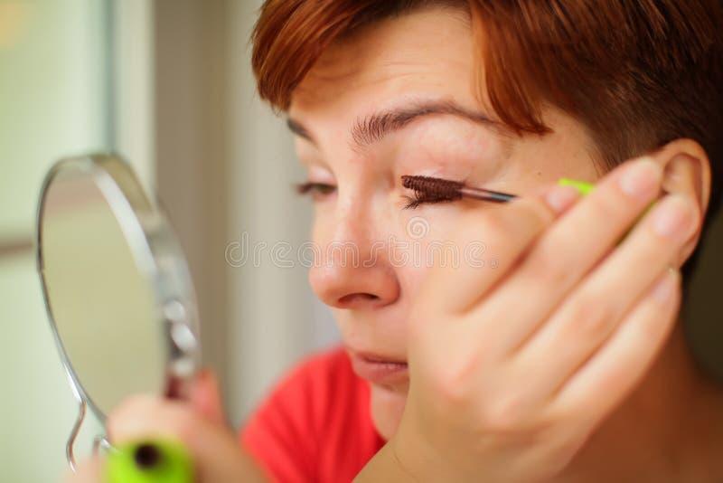 Chiuda sul ritratto della donna caucasica che mette sulla mascara marrone sui cigli Fa luce il trucco del giorno immagine stock