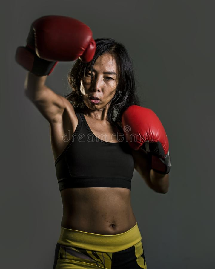 Chiuda sul ritratto della donna cinese asiatica di misura dei giovani nella cima di forma fisica e dei guantoni da pugile che get fotografia stock libera da diritti