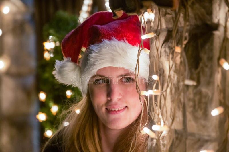 Chiuda sul ritratto della giovane donna con il cappuccio del Babbo Natale che sta la n immagini stock