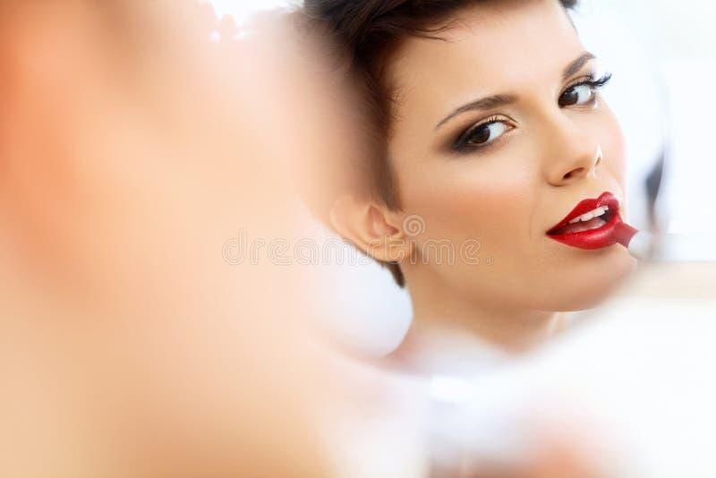 Chiuda sul ritratto della giovane donna con le labbra rosse. Bella donna che fa trucco quotidiano immagine stock libera da diritti