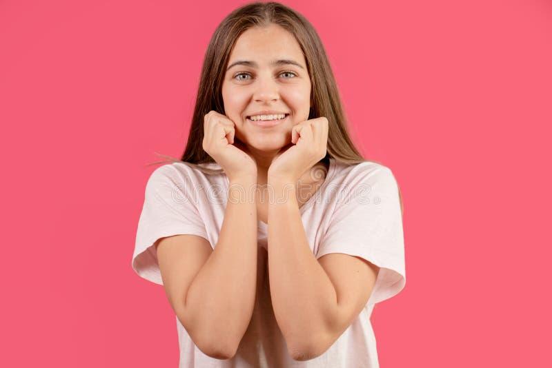 Chiuda sul ritratto della giovane donna felice con capelli lunghi che si appoggiano le sue mani fotografia stock libera da diritti