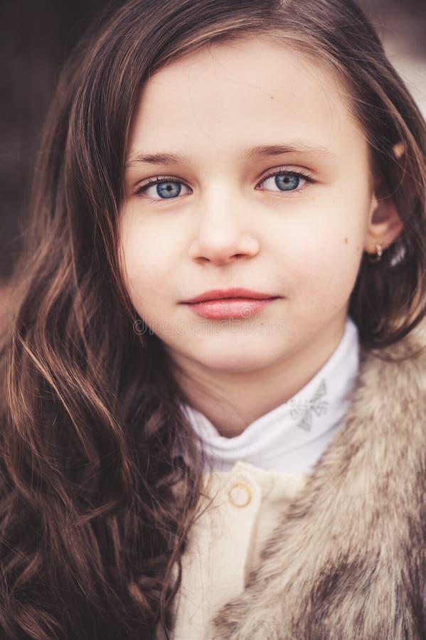 Chiuda sul ritratto della ragazza del bello bambino che esamina la macchina fotografica immagine stock libera da diritti