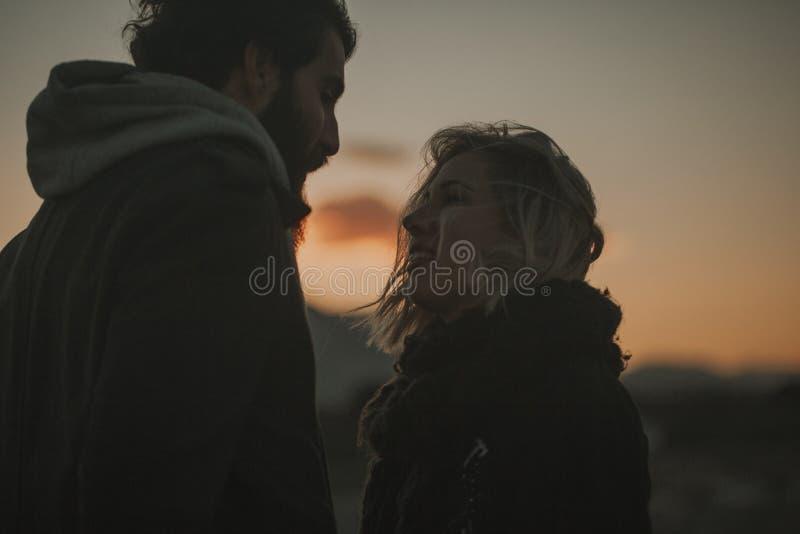 Chiuda sul ritratto delle coppie fresche che osservano l'un l'altro il tramonto con un cielo arancio nei precedenti fotografia stock