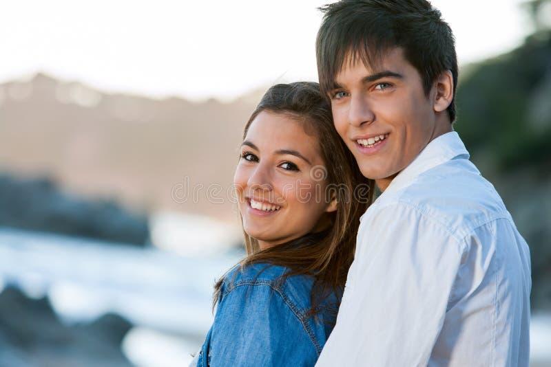 Chiuda sul ritratto delle coppie teenager alla spiaggia. fotografia stock