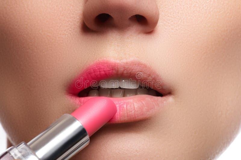Chiuda sul ritratto delle labbra attraenti di bella donna Rouging le sue labbra con il rossetto rosa del compagno La signora sta  fotografie stock libere da diritti