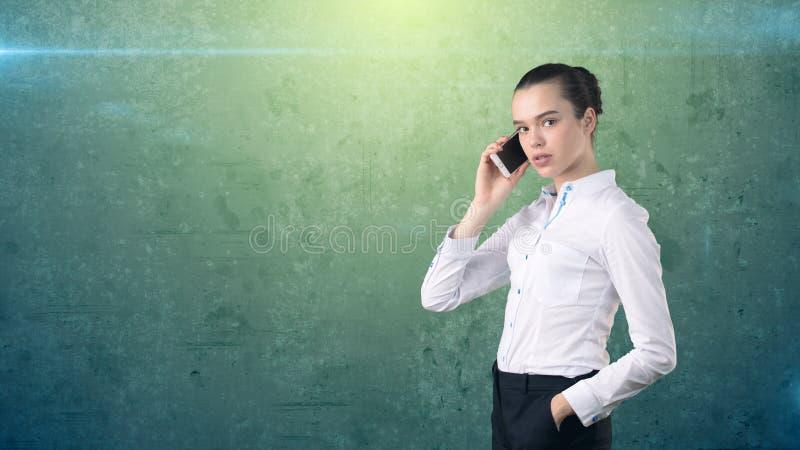 Chiuda sul ritratto di bella donna di affari, sul fare una pausa laterale e sulla conversazione sul telefono cellulare Fondo isol immagine stock libera da diritti