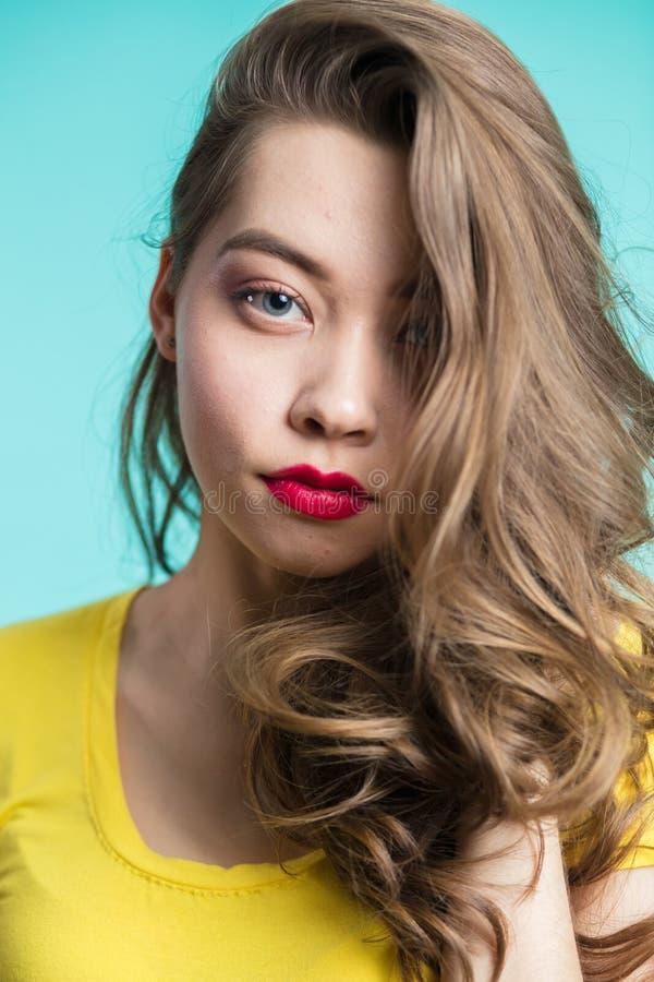 Chiuda sul ritratto di bella donna con trucco professionale, le labbra rosse ed i riccioli lunghi fotografia stock libera da diritti